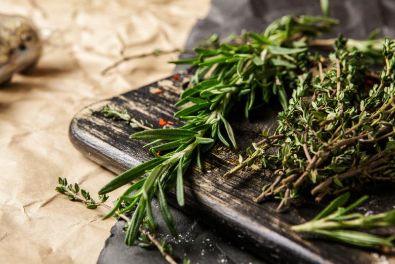 A close up image of a wooden board with dried rosemary and thyme