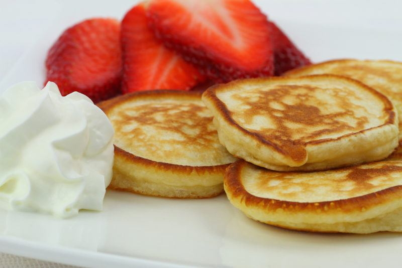 Drop scones, or pikelets, on a plate with strawberries and cream