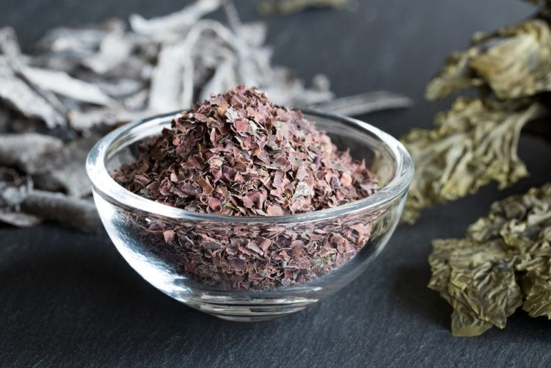 A glass bowl containing dulse with seaweed in the background