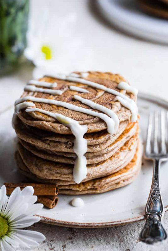 A stack of cinnamon roll pancakes with white sauce