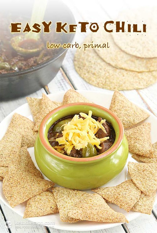 A green bowl with chili, surrounded by keto chips