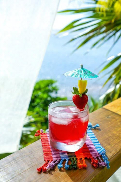 A short red cocktail on a railing overlooking the sea