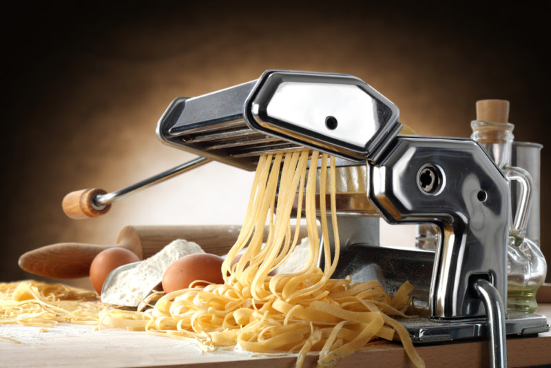 A pasta maker on a table with fressh egg pasta coming out of it