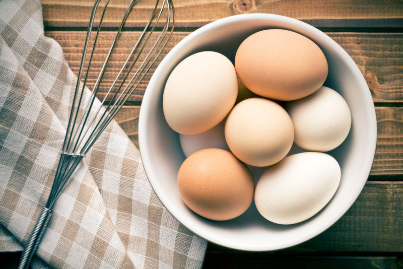 A bowl filled with eggs next to a whisk