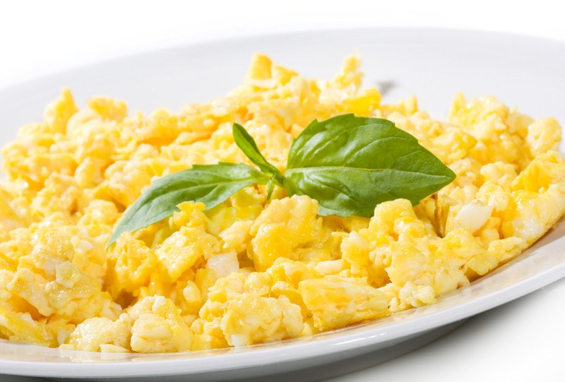 A white ceramic plate is filled with yellow scrambled eggs and a sprig of green leaves against a white background.