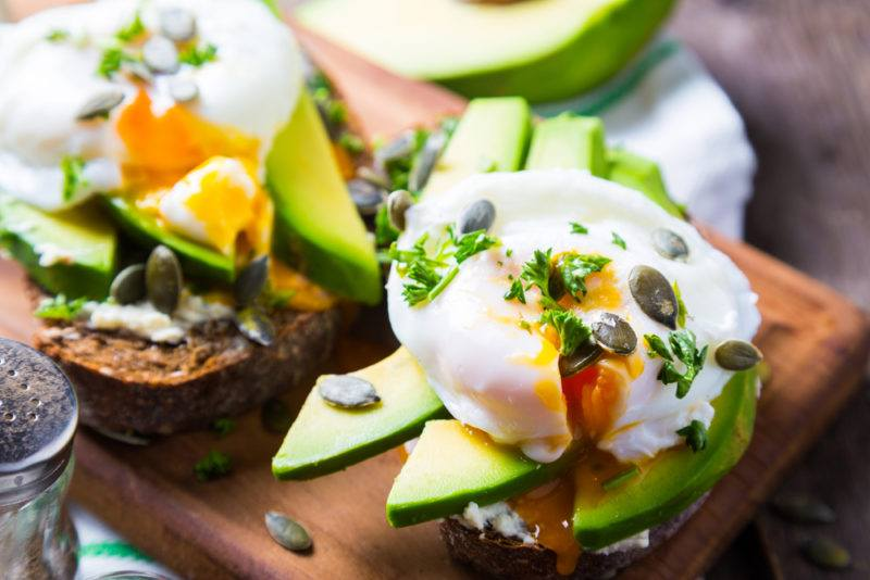 A wooden board with two pieces of toast, sliced avocado and eggs