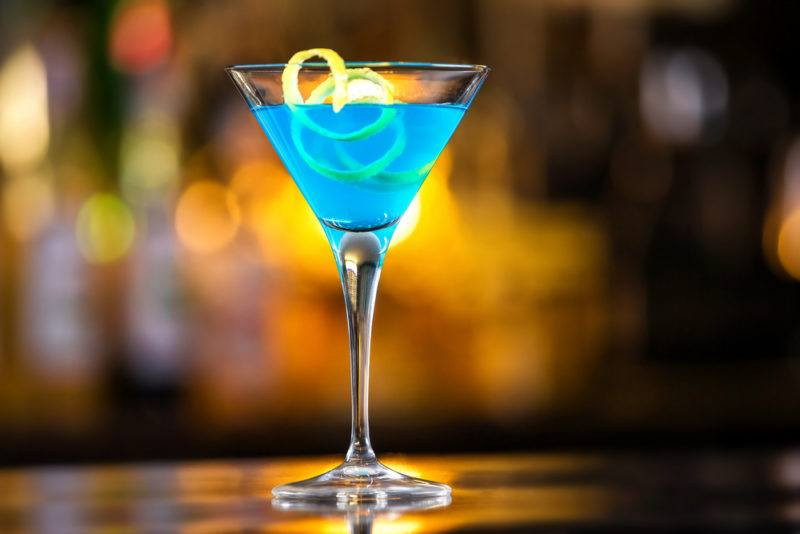 A bright blue Envy cocktail in a martini glass