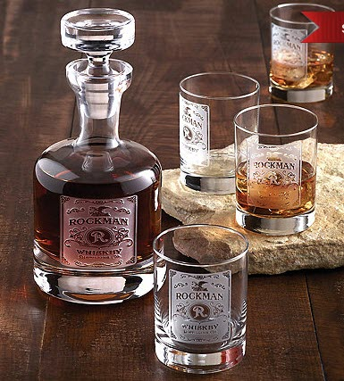 A wooden table with a whiskey decanter and four glasses.
