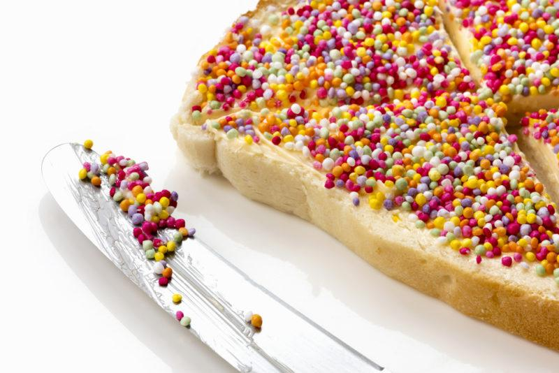 A piece of fairy bread with a knife with sprinkles