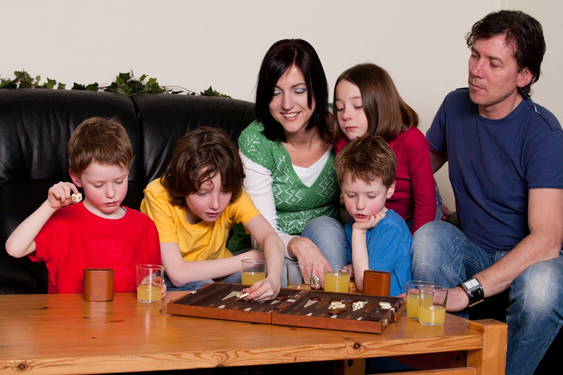 A large family sitting on a couch playing a game of backgammon