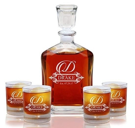 A whiskey decanter and four glasses, all engraved with a D and Drake