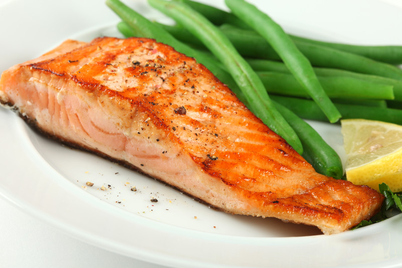 This photo shows a grilled salmon steak, green beans, and a lemon wedge on a white plate.