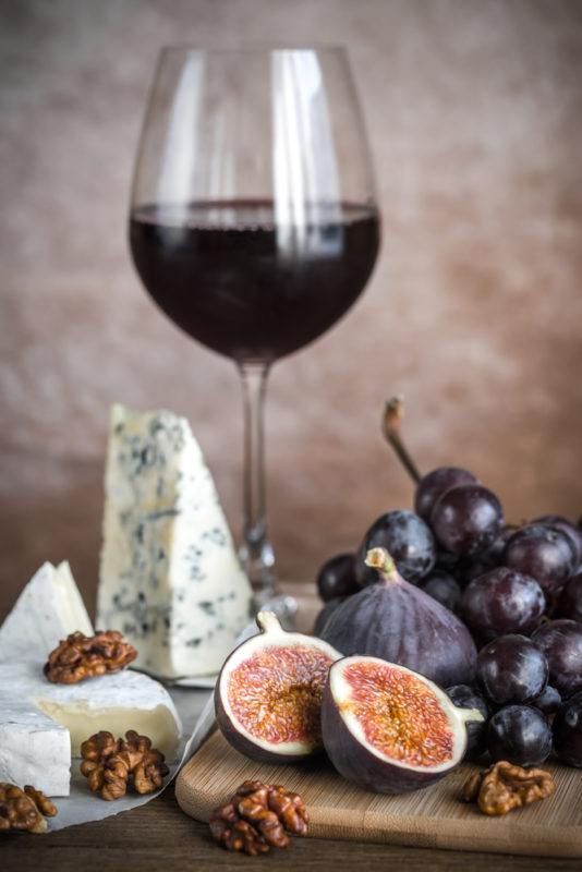 A glass of malbec red wine on a wooden board with blue cheese, walnuts, grapes, and a sliced fig
