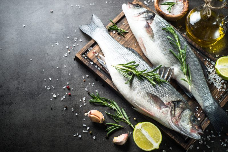 Two fresh fish on a wooden tray