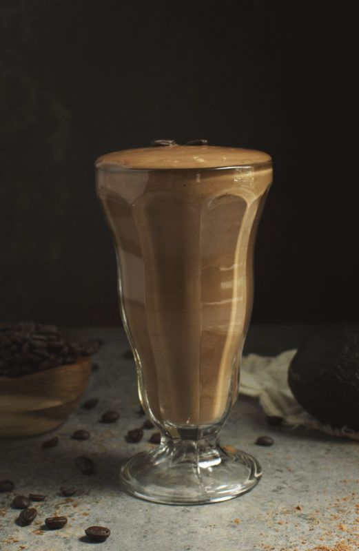 A large mocha shake in a glass against a dark background