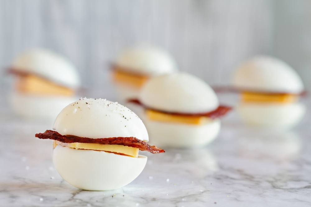 Five sandwiches made with whole eggs, with bacon and cheese in the middle
