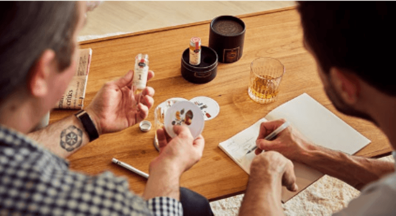 Two people sitting at a table looking at tasting notes and making personal notes as they try various samples of hard alcohol