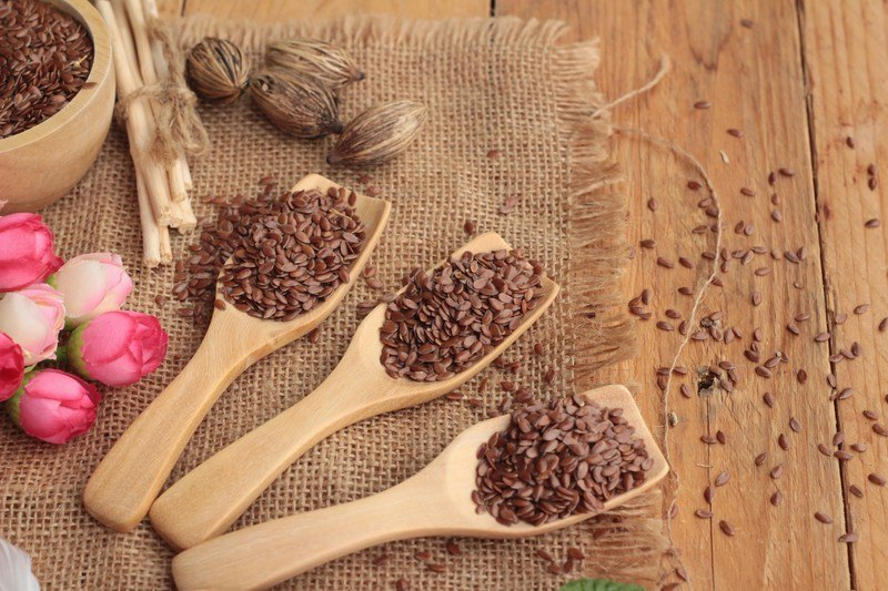 Three wooden spoons filled with flax seeds rest on a piece of burlap on a wooden table next to a bowl of flax seeds and five pink roses.