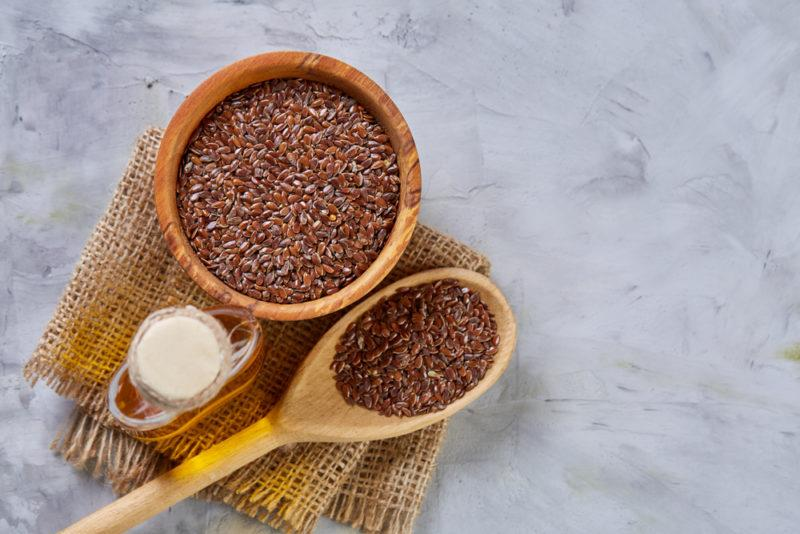 A brown bowl and spoon with flaxseeds