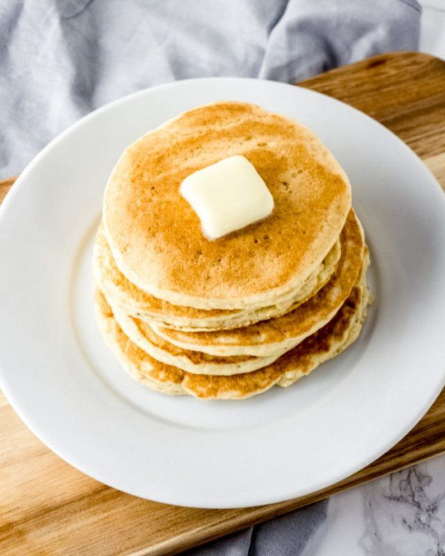 A stack of pancakes with butter on a white plate