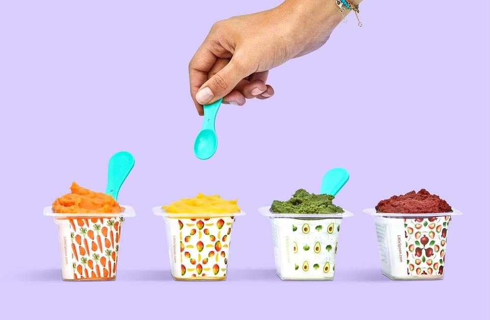 Four containers of baby food, from left to right carrot, mango, avocado, and beet  with a hand hovering over the mango baby food with a small blue spoon