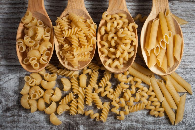 Four large wooden spoons with different types of pasta and the same types of pasta on a table