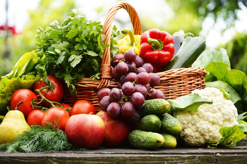 Basket full of vegetables fruits and herbs sitting on a table outside surrounded by more vegetables and fruit, including cucumbers, cauliflower, parsley, red peppers, tomatoes, and lettuce