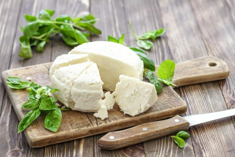 A wooden board with fresh goat's milk cheese and herbs