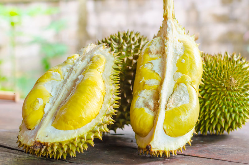 Two full durian fruit and one that has been cut in half so that the inside can be seen