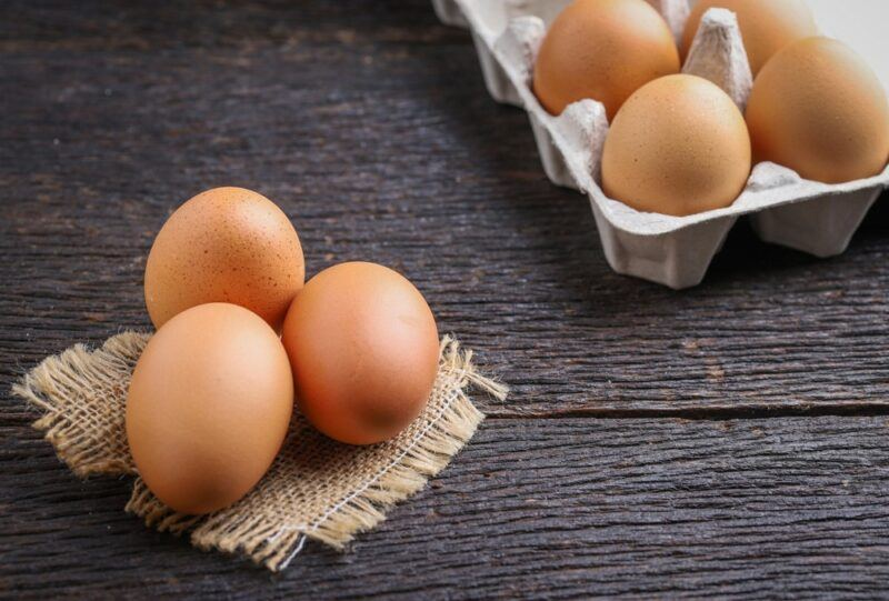 A dark table with eggs in a carton and three eggs on a cloth