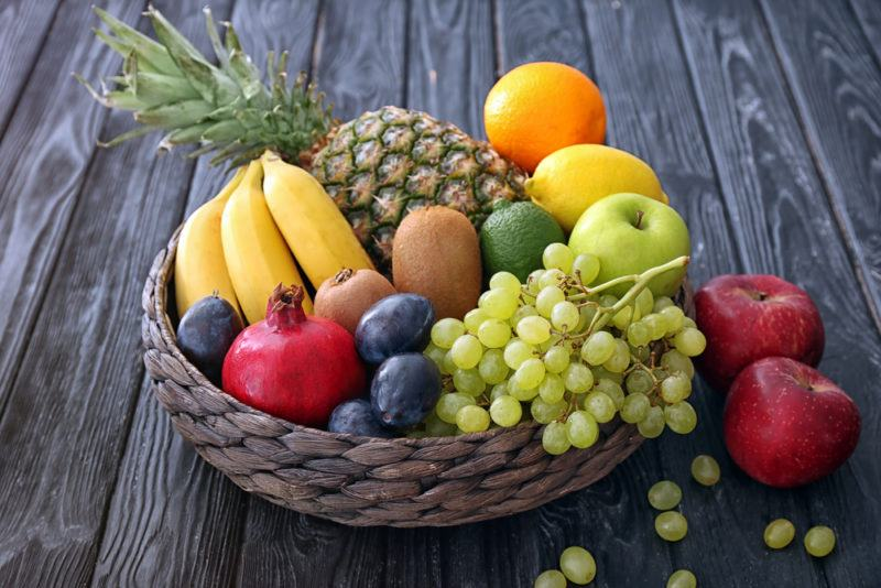 A basket of fresh fruit, including bananas, pineapple, oranges, grapes and more