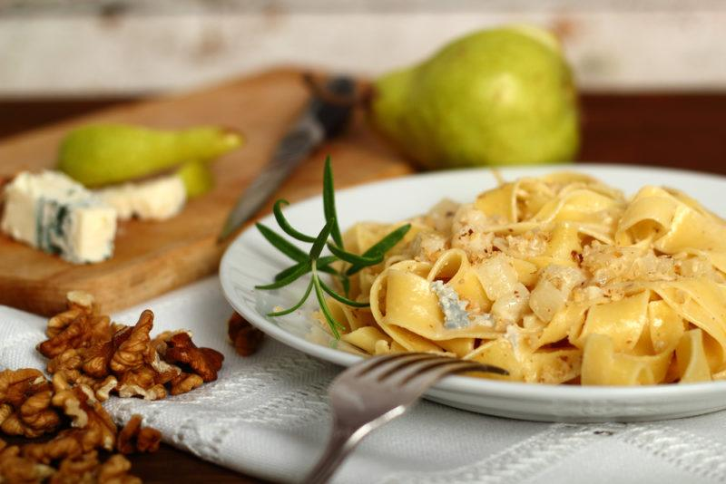 Fresh pasta with blue cheese with a fork, walnuts, blue cheese, and pears