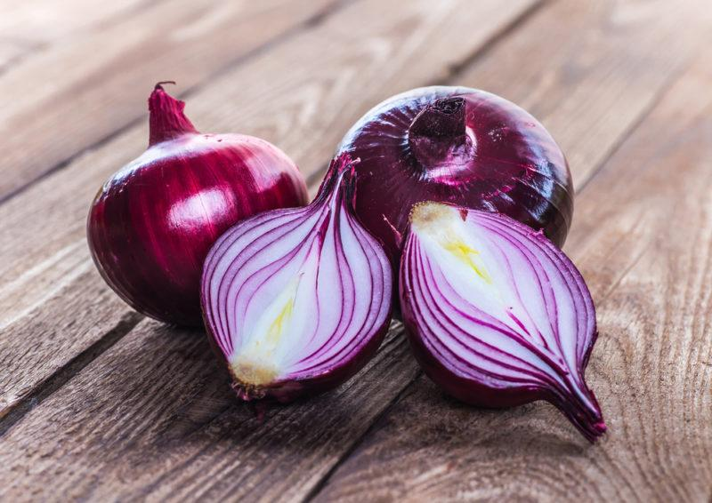 Three fresh red onions on a wooden deck, one of which has been cut in half