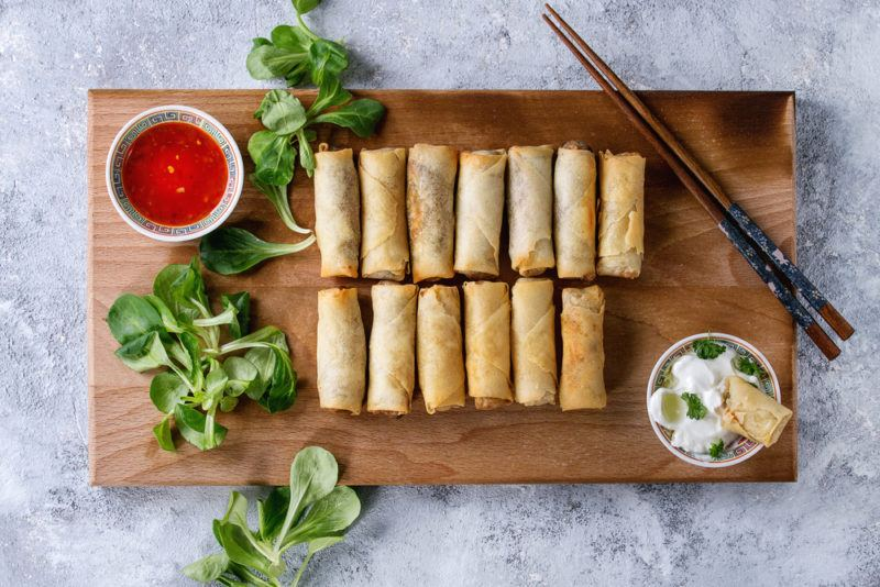 A wooden board with a dozen or so fried spring rolls with dips, greenery, and chopsticks