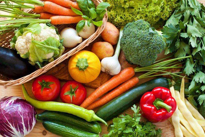 Many fresh vegetables on a table, including broccoli, carrots, and garlic
