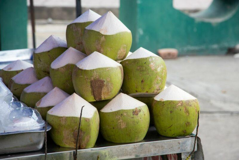 A pile of young green coconuts that have the skin cut off at the top to make them easier to stack and serve