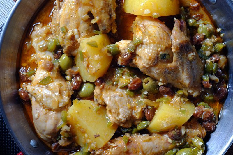 Slow Cooker Fricasse de Pollo top view with potatoes, raisins, capers, and green olives