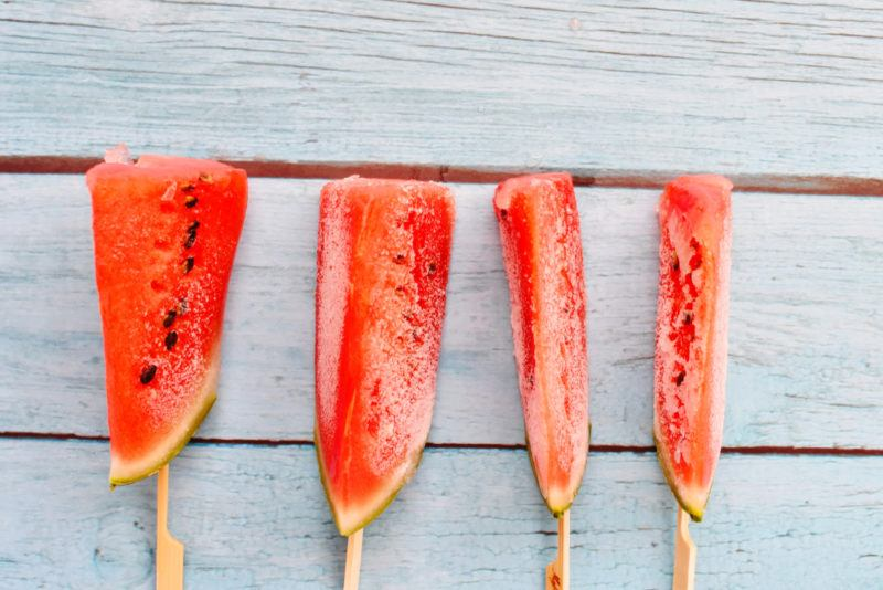 Four wedges of frozen watermelon on a stick