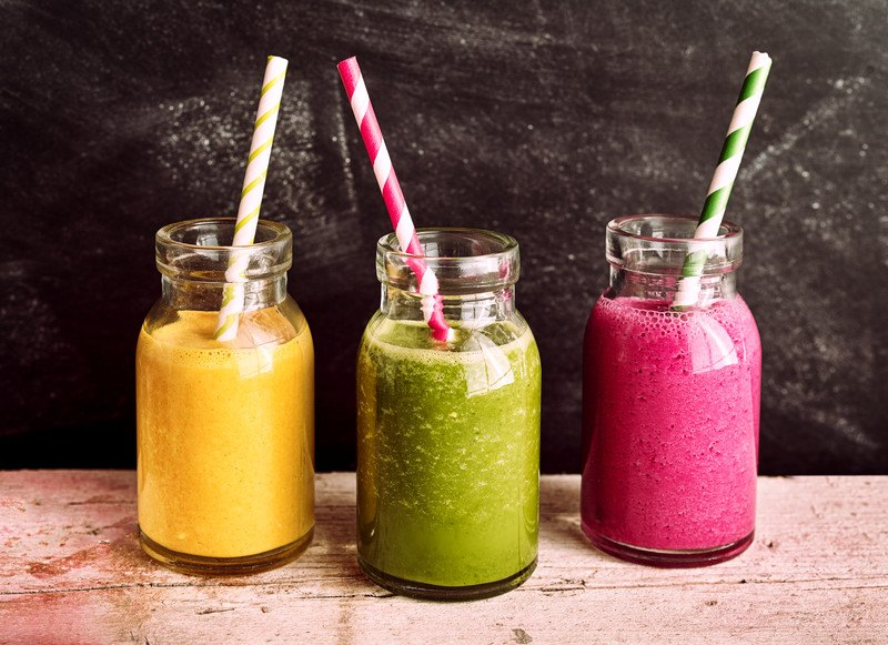Three glass jars with pureed foods in orange, green, and purple with striped straws in them rest on a wooden board.