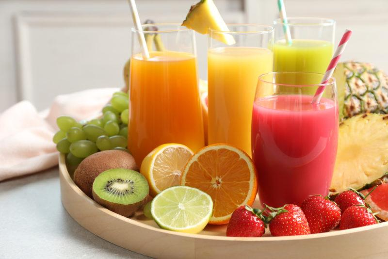 Glasses of fruit juice and fruit on a tray