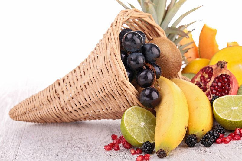 variety of fruit spilling out of cone shaped basket like grapes, kiwi, bananas, lime, and pomegranate