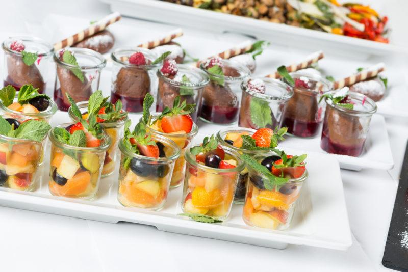 White plates on a table at a party that contain desserts, including fruit salad and chocolate mousse