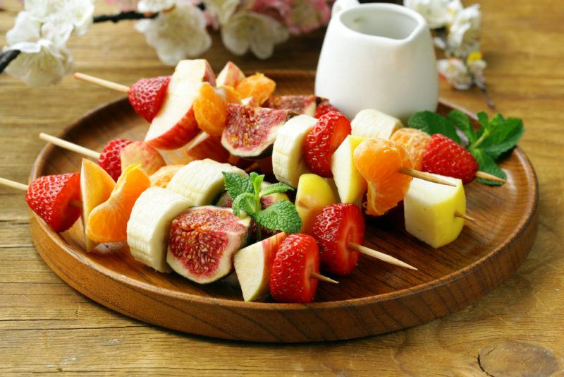 A wooden plate with skewers of fruit and cheese next to a glass of milk or some type of dip