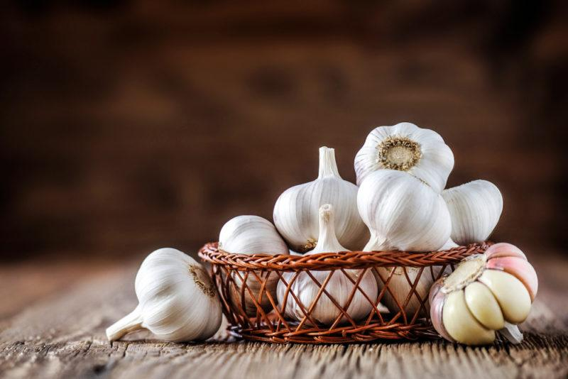A basket of garlic bulbs on a table