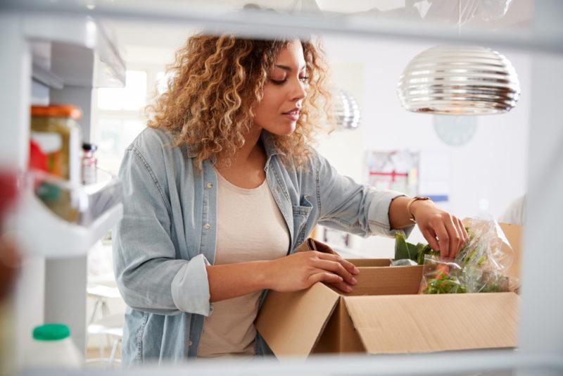 A shot through a fridge of a woman looking through her meal kit