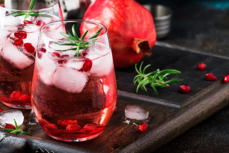 Two gin and tonics with ice and pomegranates