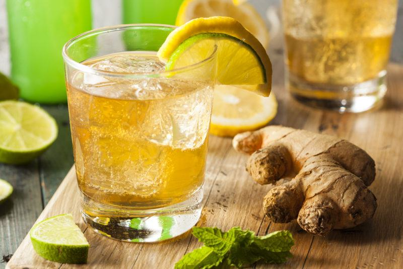 A glass of ginger ale on a wooden board with ginger and lime