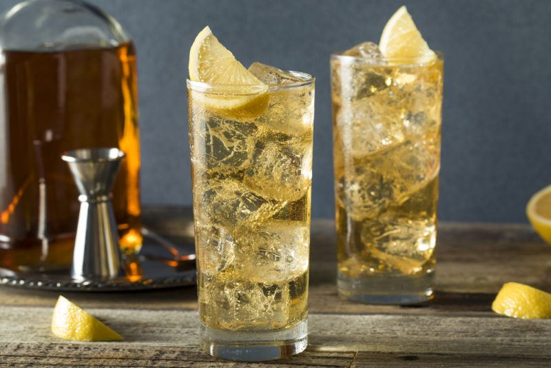 A highball glass with ginger ale, ice and lemon slices