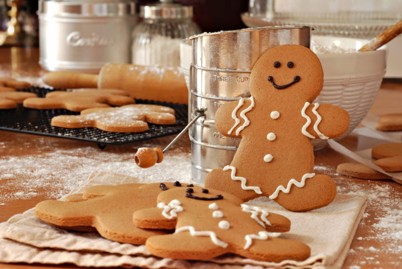 A gingerbread man standing up against a bowl, with more gingerbread men lying down flat