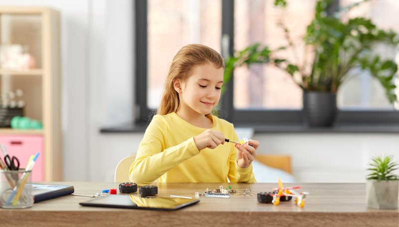 Science Kit of the Month Clubs - Young Girl sitting at desk at home working on a science project